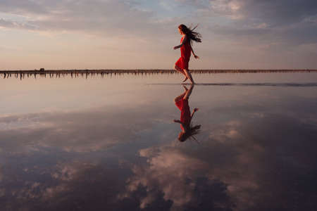Elegant woman in silky red dress walking by a salt lake. Romantic mood. Water reflection of clouds and empty space. Holiday, vacation travel scene. lake Sivash