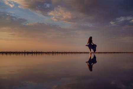 Elegant woman in silky purple dress walking by a salt lake. Romantic mood. Water reflection of clouds and empty space. Holiday, vacation travel scene. glorious sky at sunset 版權商用圖片