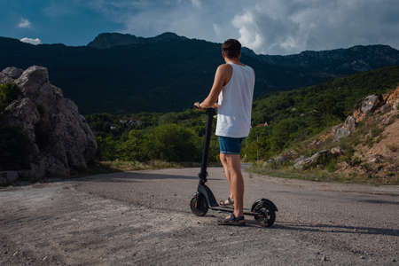 Young man riding an electric scooter on mountain range. Ecological transportation concept 스톡 콘텐츠