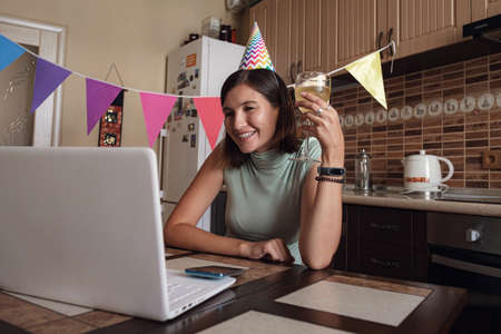 Asian woman virtual happy hour meeting birthday party with cake online, together with her friend in video conference with laptop for online meeting in video call , for social distancing