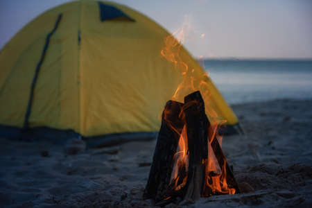 Closeup Fire in bonfire in the beach. Camping and tents to travel. Night camping on sea shore. Banque d'images