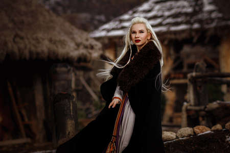 Beautiful blonde Viking dressed in a black cloak against the backdrop of the castle. beautiful film set - an ancient Viking village Stockfoto