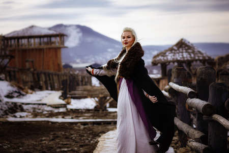 Beautiful blonde Viking dressed in a black cloak against the backdrop of the castle. beautiful film set - an ancient Viking village