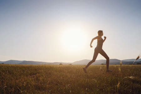 Jogging woman running in summer field at sunset. woman fitness silhouette sunrise jogging workout wellness concept.