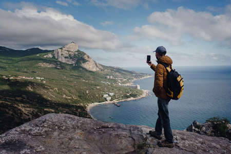 man taking photo of awesome view of mountains with smartphone. travel and discovery concept