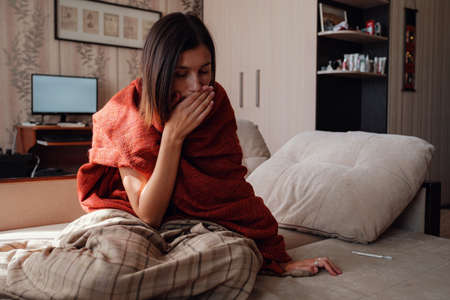 Sick and Flu Woman. Caught Cold. Woman feeling cold with blanket resting on the sofa at home Stockfoto