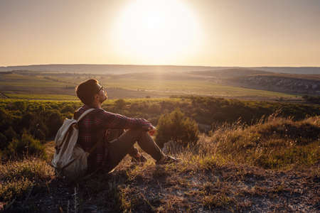 Hiker with backpack sitting on top of the mountain. Orange daybreak at horizon. Lifestyle hiking concept, summer vacations outdoor