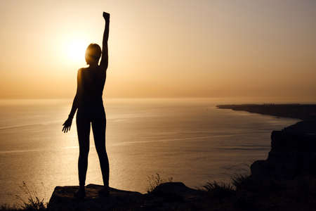 silhouette of woman with raised hands on the beach at sunset. People success, victory, and power. Strong woman, Winning, success, and life goals concept.
