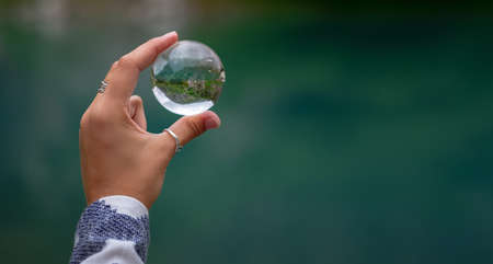A woman's hand holds a spherical glass ball against the background of a beautiful mountain lake. Turier lake, Alibek glacier, North Caucasus, Dombai ,, Russia. Zdjęcie Seryjne