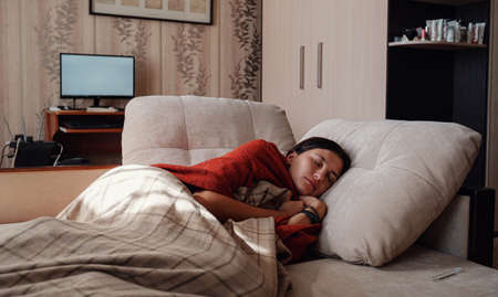 Sick and Flu Woman. Caught Cold. Woman feeling cold with blanket resting on the sofa at home