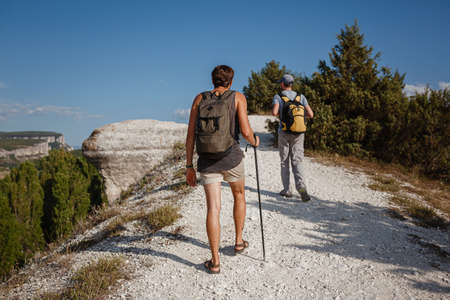 Two Men walking on rocky slope carrying Backpacks using trekking Sticks. Mountains valley View beside of People. summer travel to nature. Hiker in background. Stock fotó