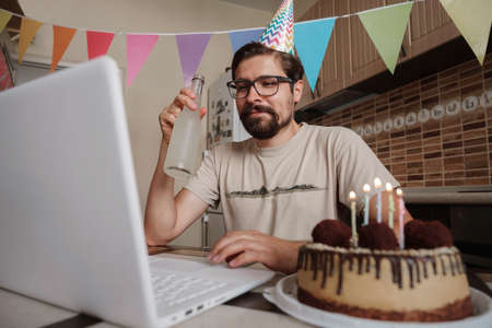 Man celebrating birthday online in quarantine time. Guy celebrating his birthday through video call virtual party with friends. Coronavirus outbreak 2020. Banco de Imagens