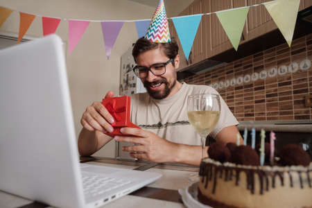 Man celebrating birthday online in quarantine time. Coronavirus outbreak 2020. The guy opens the box and is very happy with the gift. Communicating with friends remotely Фото со стока