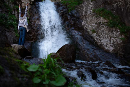 Young happy woman enjoing the waterfall. Woman standing in front of waterfall with rased hands and smile. Concept of ecotourism travel. Waterfall Shumka, Dombai, Karachay-Cherkessia, Russia