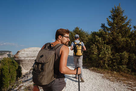 Two Men walking on rocky slope carrying Backpacks using trekking Sticks. Mountains valley View beside of People. summer travel to nature. Hiker in background.