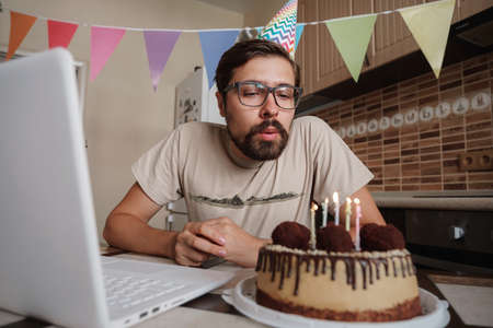 Man celebrating birthday online in quarantine time. Guy celebrating his birthday, blowing out the candle on the birthday cake and making video call. Coronavirus outbreak 2020. Фото со стока