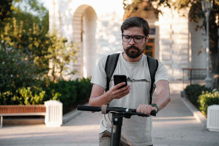 hipster man commuter with electric scooter outdoors in city, using smartphone. Young millennial guy using cellphone rental of eco transportation in summer