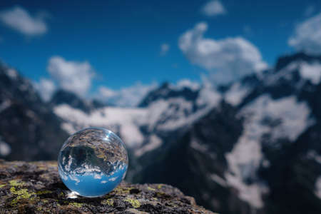 beautiful spherical glass ball with majestic Caucasian mountains, Dombai, Russia. the idea and concept of discovery, travel and trekking, Hiking theme. Banque d'images