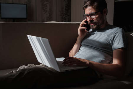 Smiling handsome freelancer working remotely from home. He is speaking on the phone. Banco de Imagens