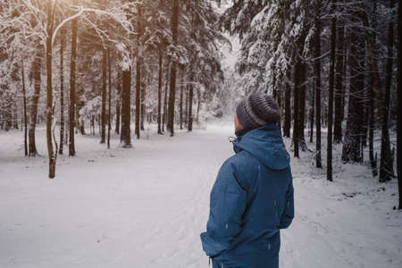 A man breathes deeply in the calm winter forest on a cold day. back view