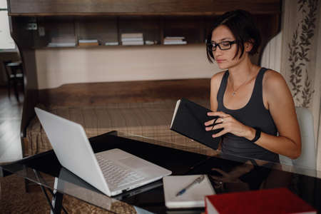 Young asian female student in glasses using laptop, communicates on internet. Cozy office workplace, remote work, E learning concept.