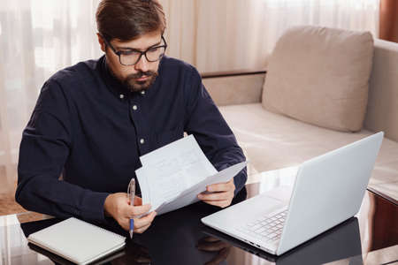 Entrepreneur in eyeglasses works with a laptop and keeps a document in a home office. Man holding paper documents, chatting online with clients on laptop at workplace.