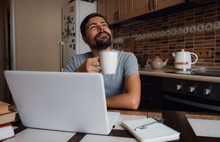 Portrait of happy man having a cup of coffee in kitchen. The guy works from home.
