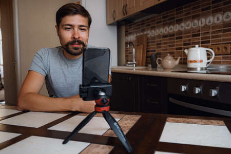 Young man having video call via smartphone in the home office. Virtual house party. confident young guy vlogger influencer shooting social media video blog talk at home