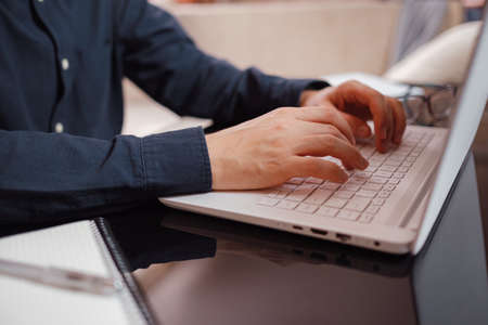 Businessman or student using laptop at home, Man hands typing on computer keyboard closeup, online learning, internet marketing, working from home, office workplace freelance concept Stock fotó