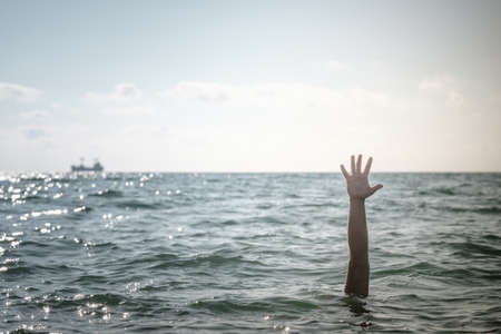 single hand of drowning man in sea asking for help. sticking out of the water