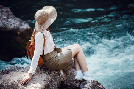 A beautiful young woman with red hair, in a hat and with a backpack near a noisy river in the forest. The idea and concept of freedom, rest, vacations, travel