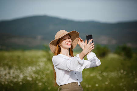 Woman using mobile phone at outdoor. Using a smartphone to navigate the route search, making photos and selfies