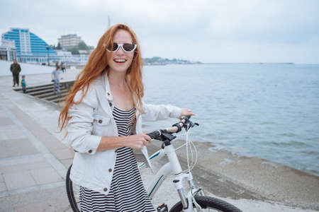 Beautiful woman riding on bike. Lifestyle and health in the city. Cheerful red-haired young woman gets pleasure from walking around the city