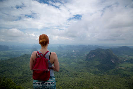 Girl enjoys a beautiful view of the valley and the Andaman Sea, islands and mountains from the viewpoint, Krabi, Thailand