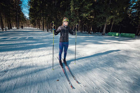 Cross-country skiing woman doing classic nordic cross country skiing in trail tracks in snow covered forest. Training track for skiers in the park of Moscow, Odintsovo
