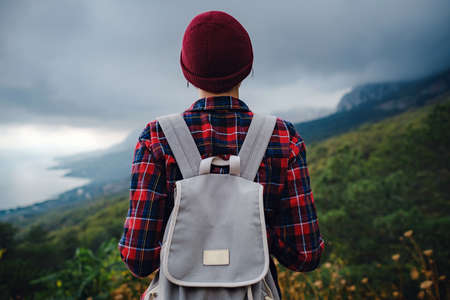 Stylish hipster asian woman with hat walking on top of mountains. Happy young woman with a backpack exploring the misty mountains. The concept of travel and wanderlust. Amazing atmospheric moment