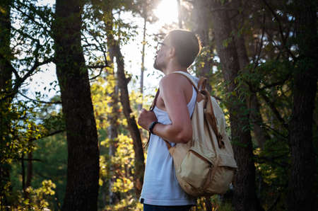 Man Traveler with backpack hiking outdoor in summer sunset forest. Travel Lifestyle and Adventure concept.