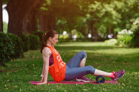 Young beautiful woman meditates on a summer day in the park. Idea and concept of calm in a busy city and a healthy lifestyle, stretching and preparing for a run in the park Zdjęcie Seryjne