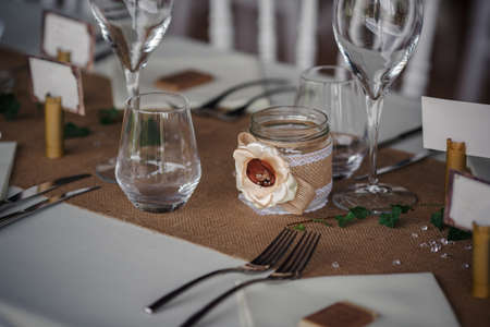 Outdoor catering dinner at the wedding with homemade garnishes decoration. Rustic and boho style decor, natural materials, figures of deer, green and brown