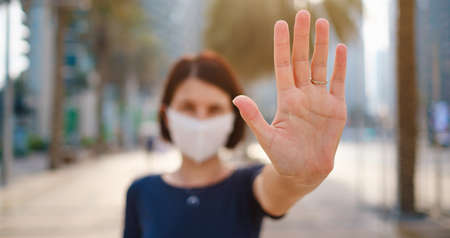 Portrait of young woman wearing in blue dress and white mask for prevent virus, walk in front of skycrapers in modern city. Gesture stop, focus on the hand