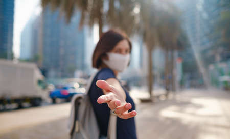 Portrait of young woman wearing in blue dress and white mask for prevent virus, walk in front of skycrapers in modern city. Gesture follow me