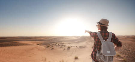 attractive asian young woman in plaid shirt in desert, treveling in UAE on safari, wearing hat and backpack, exploring nature of sandy beauty 免版税图像