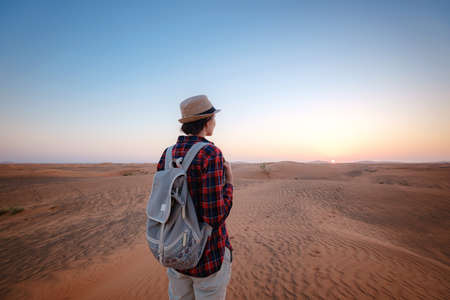 attractive asian young woman in plaid shirt in desert, treveling in UAE on safari, wearing hat and backpack, exploring nature of sandy beauty. making selfie in the background of the sunset