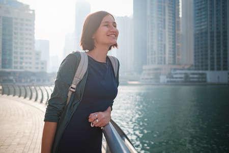 Happy young female traveler in the big city of Dubai, famous place Dubai marina. Luxury and comfortable tourism season in United Arab Emirates. 免版税图像