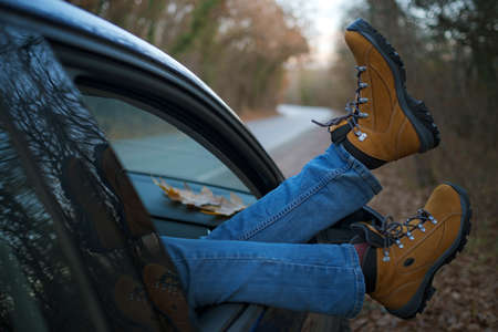Woman feet in trendy yellow hiking boots on car door. Feet outside the window at sunset forest. The concept of freedom of movement. An autumn weekend in nature.