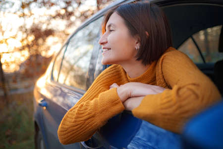 Cheerful asian woman in a car on sunset. the idea and concept of travel, discovery and recreation holiday