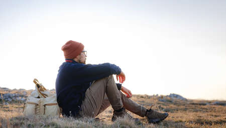 A young man sitting in spring mountains at sunset and enjoying view of nature. Mountain and coastal travel, freedom and active lifestyle