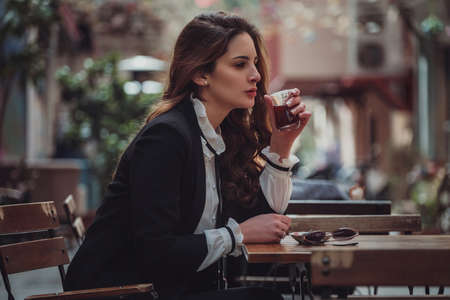 A latin woman walks through old Middle Eastern town. Female traveler in Istanbul and and drink turkey tea in cafe, Beyoglu district, Istanbul, Turkey. 免版税图像