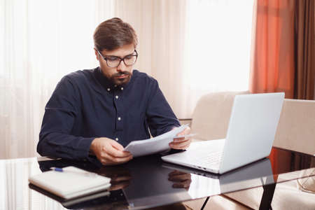 Entrepreneur in eyeglasses works with a laptop and keeps a document in a home office. Man holding paper documents, chatting online with clients on laptop at workplace. 免版税图像