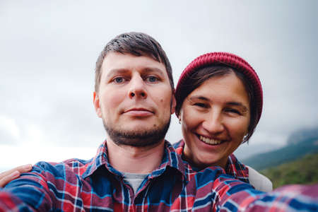 Happy couple taking selfie self-portrait photo hiking. Two friends or lovers on hike smiling at camera outdoors mountains. a beautiful multiracial couple of hipster 免版税图像
